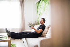 Man sitting on a sofa watching tv holding remote control at home Royalty Free Stock Image