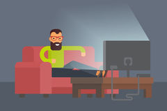 Man sitting on sofa watching tv at home.  Stock Photo