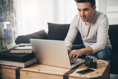 Man sitting on a sofa working on laptop Royalty Free Stock Image