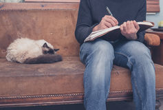 Man sitting on sofa writing ion notebook. A young man is sitting on a sofa with a cat and is writing in a notebook Royalty Free Stock Photo