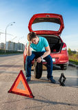 Man sitting on spare wheel near broken car Royalty Free Stock Photography