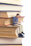 Man sitting on a stack of books Royalty Free Stock Photography