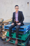 Man sitting on a stack of pallets. Well dressed man sitting on a stack of pallets royalty free stock photo