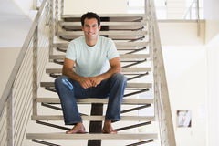 Man sitting on staircase smiling Stock Photography
