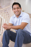 Man sitting on staircase smiling Royalty Free Stock Image