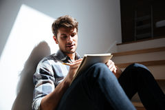 Man sitting on stairs at home and writing in notepad. Attractive young man in checkered shirt and jeans sitting on stairs at home and writing in notepad Royalty Free Stock Images