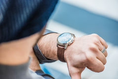 Man sitting on stairs and looking at his watch - close up view of the watch Royalty Free Stock Images