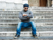 Man sitting on stairs and looking at his watch Stock Image
