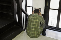 Man sitting in stairwell Stock Images