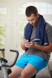 Man sitting on stationary bike stock photo