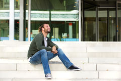 Man sitting on steps listening to music Royalty Free Stock Photo