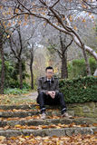 Man sitting on steps at a park in fall season / autumn. With orange and green leaves, trees and plants royalty free stock images