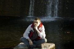 Man sitting on a stone Royalty Free Stock Photos