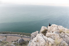 Man sitting stone cliff above lake sea. Stock Photo