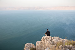 Man sitting stone cliff above lake sea. Stock Photos