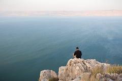 Man sitting stone cliff above lake sea. Stock Photos