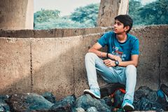 Man Sitting on Stone Leaning on Concrete Wall stock photo
