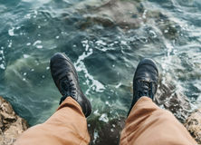 Man sitting on stone over the sea Stock Photography