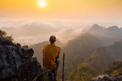 Man sitting on stone top of high mountain Stock Photo