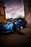 Man sitting on street leaning to blue sportcar Stock Photo