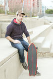 Man sitting in the street with skateboard. Stock Photo