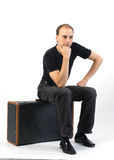 Man sitting on suitcase royalty free stock photos