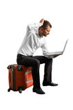 Man sitting on suitcase and looking at laptop Stock Image