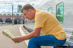 Man sitting on a suitcase at the railway station. And is studying the map Royalty Free Stock Images
