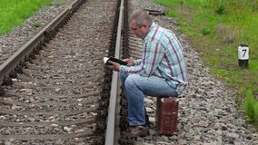 Man sitting on suitcase and reading book near railway. In summer day stock footage