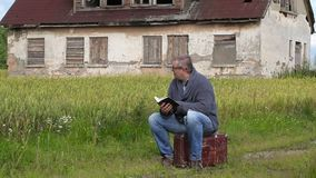 Man sitting on suitcase and reading book. In summer day stock footage