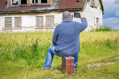Man sitting on suitcase and take pictures of old house Royalty Free Stock Images