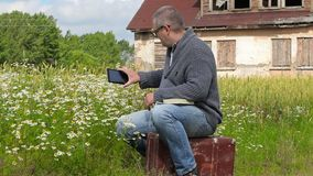 Man sitting on suitcase and take pictures on tablet PC near chamomile flowers. In summer day stock footage