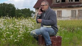 Man sitting on suitcase and talking on phone near chamomile flowers. In summer day stock video