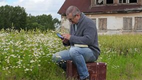 Man sitting on suitcase and using tablet PC. In summer day stock video footage