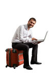 Man sitting on suitcase and working Royalty Free Stock Image