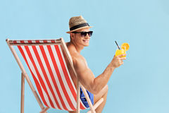 Man sitting in a sun lounger and holding a cocktail Stock Photos