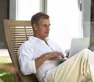 A man sitting on a sun lounger using a laptop Stock Images