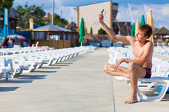 Man sitting on a sunbed, with mobile phone in hand Royalty Free Stock Image