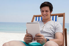 Man sitting on sunlounger and using digital tablet on the beach. Smiling man sitting on sunlounger and using digital tablet on the beach Royalty Free Stock Photos