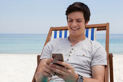 Man sitting on sunlounger and using mobile phone on the beach. Smiling man sitting on sunlounger and using mobile phone on the beach Stock Image