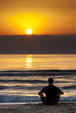 Man Sitting Sunrise Sunset Beach Contemplation. Young man sitting on the beach contemplating sunrise sunset behind wall of clouds stock image