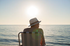 Man sitting sunset beach backlight lens flare Stock Photos