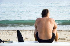 Man sitting on surfboard at beach. A mature man is sitting on his surboard at the beach and looking out to sea in a pensive mood Royalty Free Stock Image
