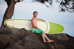 Man Sitting with Surfboard Stock Image