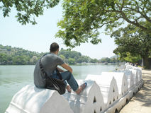 Man Sitting On Surrounding Wall By River Stock Photo