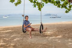 The man is sitting on a swing and listening to music. Lifestyle concept. Thailand, Krabi. February 2017. The man is sitting on a swing and reading an e-book Stock Images