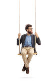 Man sitting on a swing and looking to the right. Isolated on white background Stock Images