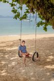 The man is sitting on a swing and reading an e-book. Lifestyle concept. Thailand, Krabi. February 2017. The man is sitting on a swing and reading an e-book Stock Photo