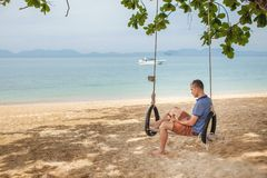 The man is sitting on a swing and reading an e-book. Lifestyle concept. Thailand, Krabi. February 2017. The man is sitting on a swing and reading an e-book Royalty Free Stock Photos