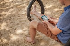 The man is sitting on a swing and reading an e-book. Lifestyle concept. Thailand, Krabi. February 2017. The man is sitting on a swing and reading an e-book Royalty Free Stock Photo